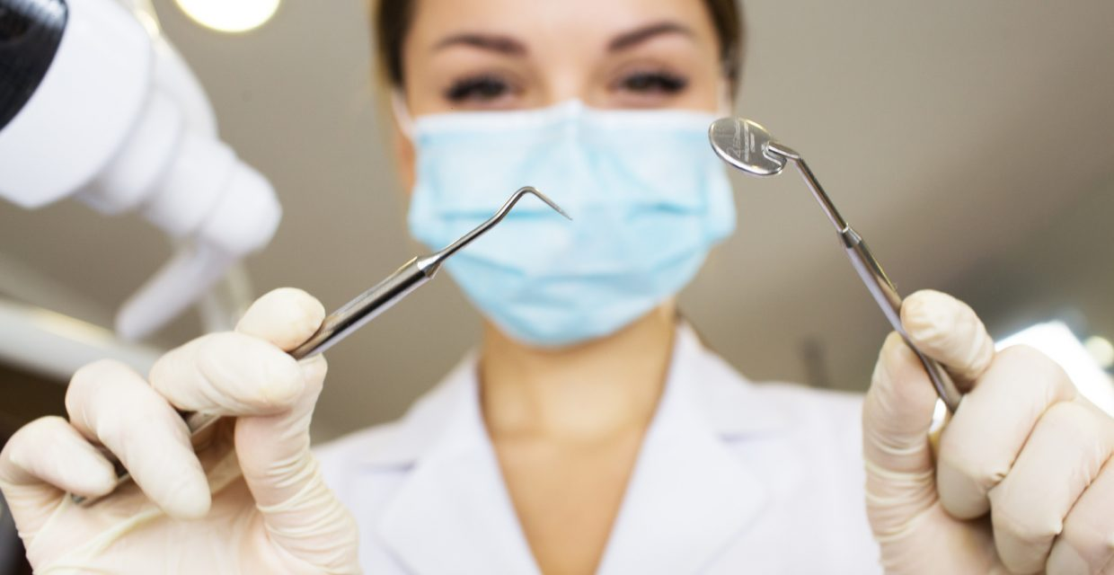 young women dentist with sterile mask readily approaching a patient with dental instruments held in the hands protected with surgical gloves young dentist with sterile mask.Dentist
